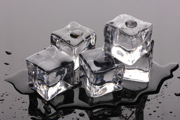 Melting ice cubes on grey background