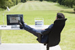 Businessman with feet up sitting at desk in field