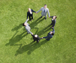 Business people holding hands in a circle outdoors