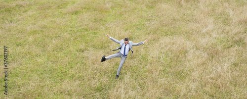 Businessman jumping in field