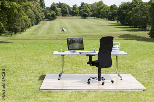 Office desk and chair outdoors in field
