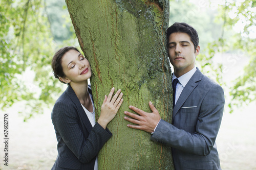 Business people hugging tree