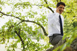 Businessman sitting in tree talking on cell phone