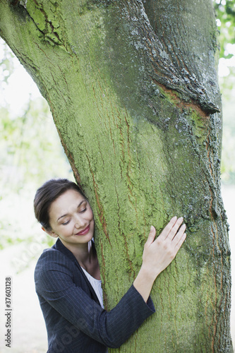 Businesswoman hugging tree