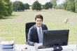 Businessman sitting at desk outdoors