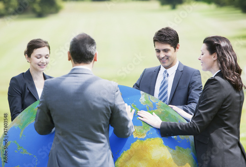 Business people standing outdoors with large ball