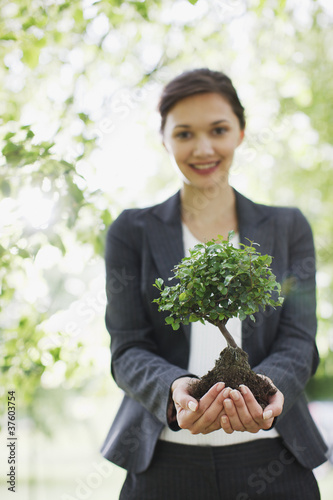 Businesswoman standing outdoors holding plant