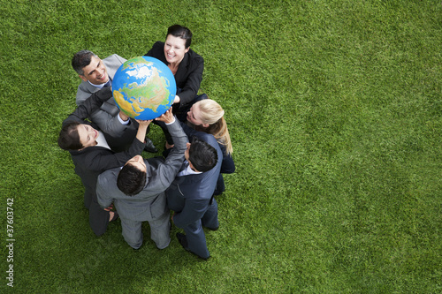 Business people lifting globe together outdoors