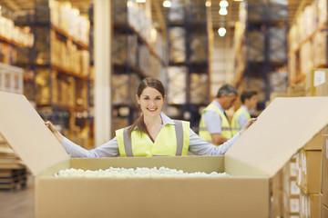 Woman in warehouse closing cardboard box