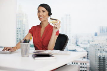 Businesswoman holding credit card at office desk