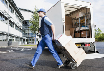 Deliveryman puling boxes on hand truck