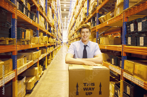 Worker standing in warehouse with box