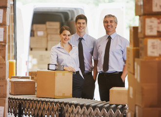 Business people standing with boxes in shipping area
