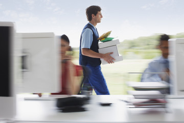 Deliveryman walking with packages in office