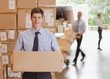 Businessman holding box in warehouse