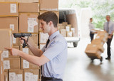 Businessman using scanner on box in warehouse