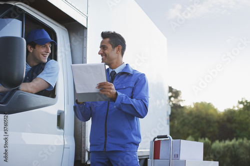 Deliveryman talking with worker holding clipboard