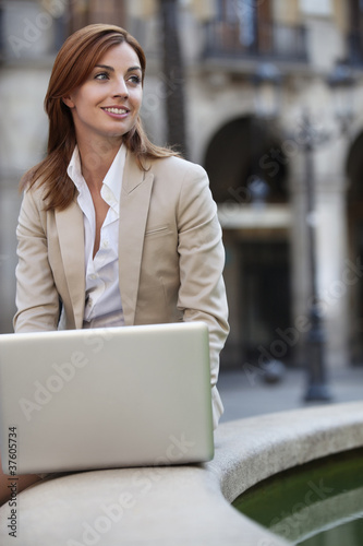 Businesswoman sitting by fountain using internet