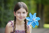 Smiling girl holding pinwheel outdoors