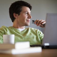 Man sitting with laptop thinking