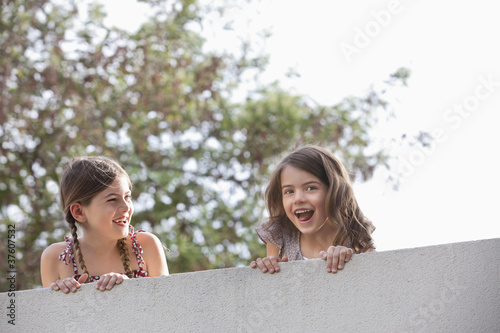 Girl watching friend screaming over wall