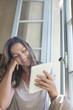 Smiling woman using digital tablet
