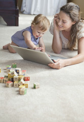 Mother and daughter using laptop on floor