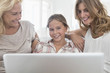 """Grandmother, mother and daughter using laptop"""