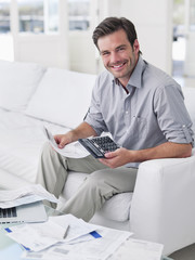 Man sitting on sofa paying bills