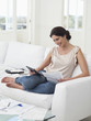 Woman sitting on sofa paying bills