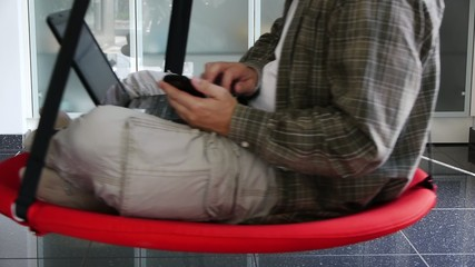 Male - Working with Notebook and Mobile in Swinging Seat