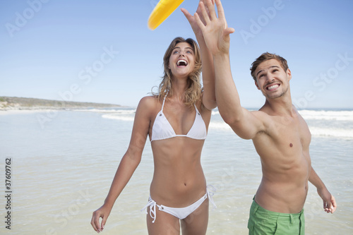 Couple catching plastic disc on beach