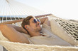 Man laying in hammock listening to mp3 player