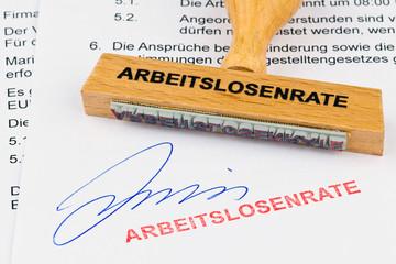 Holzstempel auf Dokument: Arbeitslosenrate