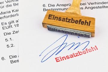 Holzstempel auf Dokument: Einsatzbefehl