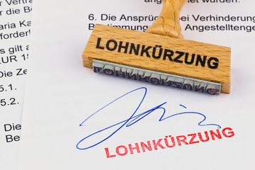 Holzstempel auf Dokument: Lohnkürzung