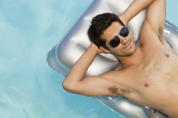 Man floating in swimming pool sunbathing