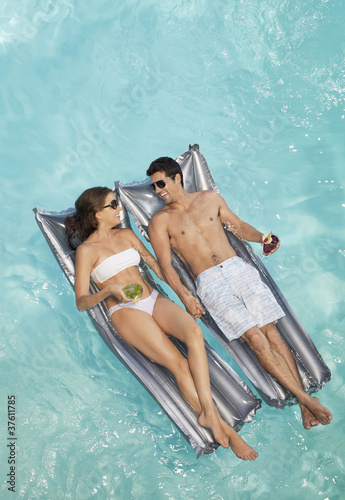 floating in pool with drink