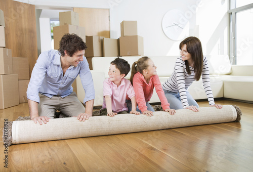 Family unrolling carpet together in new home