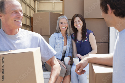 Woman drinking coffee on back of moving van