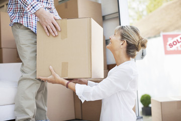 Husband handing box to wife from moving van