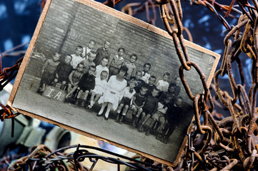 Photo of sad children in a group between rusty chains