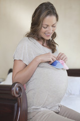 Expectant mother holding baby booties