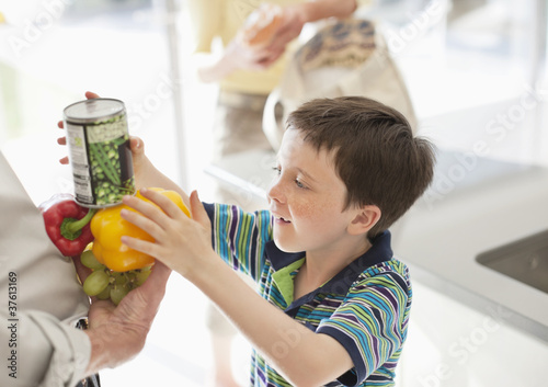 Boy stacking food into grandfather?s hands