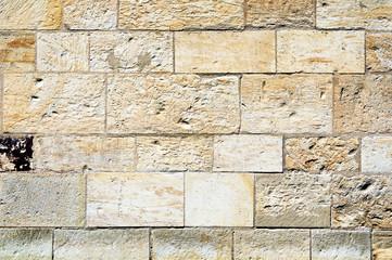 Fragment of a stone wall made of limestone bricks