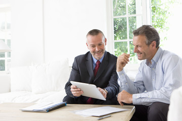 Financial advisor showing digital tablet to customer