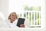 Woman reclining on sofa using digital tablet