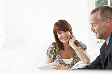 Financial advisor showing digital tablet to client