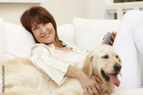 Woman sitting with dog on sofa using digital tablet