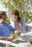 Couple relaxing together in backyard with digital tablet